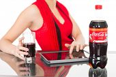 NAKHODKA, RUSSIA - JANUARY 18, 2014: Girl holding a glass of Coca-Cola on the table is a bottle of C