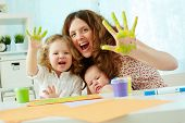 stock photo of waving hands  - Portrait of a happy family having fun painting with palms and fingers - JPG