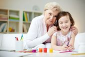 stock photo of grandmother  - Portrait of happy girl and her grandmother looking at camera at home - JPG