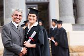 foto of white gown  - pretty female graduate with her father at university graduation - JPG