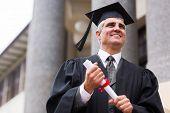 optimistic senior university graduate in front of college building