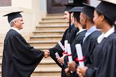 group of cheerful graduates in line handshaking with dean