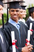 smiling african american male graduates standing with classmates in a row