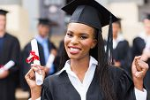 happy african american female graduate at university graduation ceremony