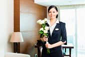 Hotel Manager or director or supervisor welcome arriving VIP guests with roses on arrival in luxury or grand hotel
