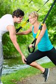 Fitness woman exercising with suspension trainer and personal sport trainer in City Park under summe