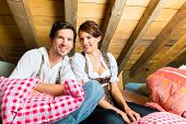 Young couple in bed on the floor of a barn or a mountain hut in the Alps enjoying the leisure time