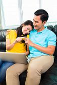 Young Asian handsome man spend girlfriend online shopping with credit card