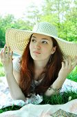 Thoughtful beautiful redheaded woman looking away in a white summer hat outdoors