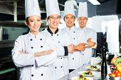 Asian Indonesian and Chinese chefs along with other cooks in restaurant or hotel commercial kitchen