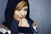 Closeup portrait of thoughtful young woman in hooded sweater, smiling