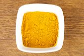 Curcuma, curry, yellow- orange spice in a bowl. Over wooden background.