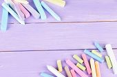 Chalks in variety of colors, on wooden background