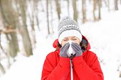 A picture of a young woman blowing her nose in the winter forest
