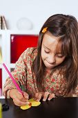 Little girl at her home drawing with a pencil