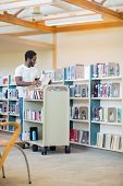 Full length of young male librarian with trolley arranging books in library