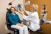 Female eye specialist adjusting phoropter for senior woman
