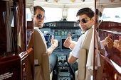 Portrait of confident pilots gesturing thumbs up in cockpit of private jet