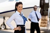 Portrait of attractive airhostess with pilot and private jet in background at terminal