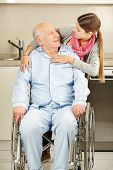 Happy young woman embracing a senior man in wheelchair