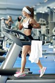 stock photo of treadmill  - Smiling athletic woman running on a treadmill - JPG