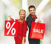sale, shopping and mall concept - smiling man and woman with shopping bag at shopping mall