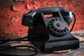 image of rotary dial telephone  - Close up side view of an old classic black dial - JPG