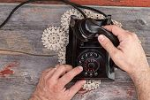 picture of rotary dial telephone  - High angle view of the hands of a married man dialing out on an old rotary telephone standing on a weathered rustic table top - JPG