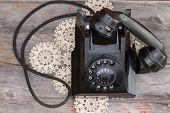picture of rotary dial telephone  - Old rotary telephone with the handset off the hook standing on a decorative patterned crocheted doily on a rustic weathered wooden table - JPG