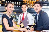 Asian couple tasting red wine in wine shope