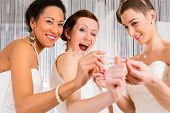 Women having fun while bridal gown fitting in wedding fashion store