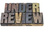 under review - isolated word in vintage letterpress wood type with ink patina