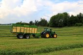 John Deere 6210R Tractor And Full Krone Mx 350 Gl Forage And Discharge Wagon, Motion Blur