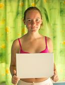 Cute girl holding clean white sheet paper (banner for your message)