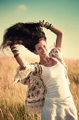 happy smiling woman in boho style clothes with flying hair in summer field retro colors