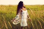 woman wearing boho style clothes in the field , hot summer day, retro colors