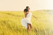 happy smiling woman in boho style clothes run  through the field, sunny summer day