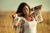 smiling young  woman wearing boho style clothes enjoy in summer day on the field of grass, retro col