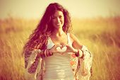 picture of shapes  - smiling young woman in summer field show heart shape hands sign - JPG