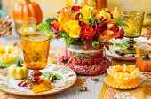 Festive table setting with basket of autumn flowers,candle and pumpkin