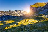 Mountains glow by morning sunlight with shacks in the national park Durmitor in Montenegro, Balkans.