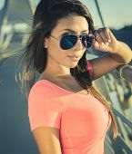 Beautiful young woman wearing pink top and sunglasses.  Image cross processed