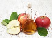stock photo of vinegar  - Apple cider vinegar and fresh apple on a wooden background