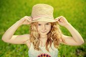 Portrait of a happy summer girl in straw hat. Happy childhood. Countryside.