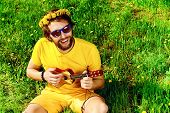 Happy carefree young man sitting on a grass and playing his little guitar. Summer, freedom, hippie.