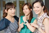 Asian woman using wearable watch and showing to her friends.