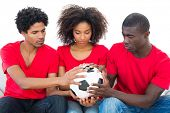 Football fans in red holding ball together on white background