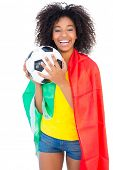 Pretty football fan with portugal flag holding ball on white background