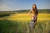Girl with dog  in a wheat field at sunset