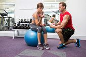 Personal trainer with client sitting on exercise ball lifting dumbbell at the gym